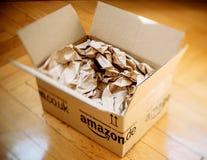 Pacchetto di Amazon aperto sul pavimento di parquet domestico Fotografie Stock