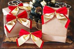 Pacchetto di carta dei regali con l'arco dorato rosso vicino al piccolo tre di Natale Fotografia Stock