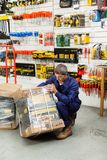 Pacchetto di sollevamento dello strumento del lavoratore nel negozio dell'hardware Immagini Stock