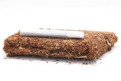 Pacchetto isolato tabacco di rotolamento della mano con la sigaretta fotografie stock
