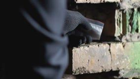 Pacchetto nascondentesi della cocaina del commerciante in foro del muro di mattoni, contrabbando, primo piano delle mani archivi video