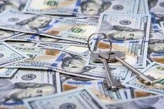 Pacco delle chiavi sul fondo delle banconote in dollari Fotografia Stock