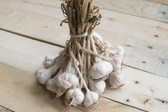 Pacco delle lampadine dell'aglio legate insieme sui pannelli di legno Immagini Stock
