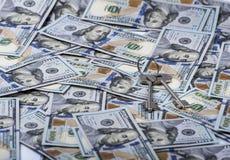 Pacco e un mucchio chiave di cento banconote in dollari Immagine Stock
