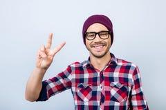 Pace! I giovani pantaloni a vita bassa alla moda nerd sorridenti dello studente gesturing immagini stock libere da diritti