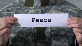 Pace scritta su carta in mani del soldato maschio, conclusione della guerra, riconciliazione video d archivio