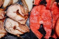 Paces grandes de los diversos pescados salados que mienten en la placa negra imagen de archivo
