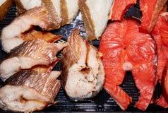 Paces grandes de los diversos pescados salados que mienten en la placa negra fotografía de archivo libre de regalías