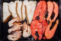 Paces grandes de los diversos pescados salados que mienten en la placa negra imagenes de archivo