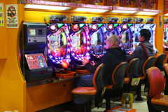 Pachinko players in Tokyo. Pachinko is a type of mechanical game originating in Japan and is used as both a form of recreational arcade game and much more Stock Photos