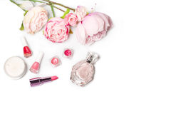 Pachnidło butelka, gwoździa połysk, pomadka Mody kobiety wciąż życie Strzela żeńskie rzeczy z kwiatami na białym tle Fotografia Stock