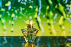 Pachnidło butelka na złotym i zielonym tle zdjęcie stock