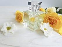 Pachnidło butelki koloru żółtego róża błyszcząca na drewnianej dekoraci obrazy stock