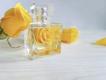 Pachnidło butelki koloru żółtego róża na drewnianym zdjęcie stock