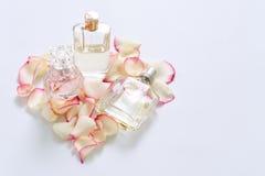 Pachnidło butelki z kwiatów płatkami na lekkim tle Mydlarnia, woni kolekcja Kobiet akcesoria Obraz Royalty Free