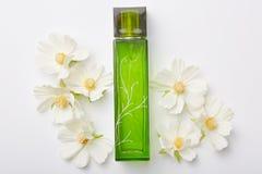 Pachnidło dla kobiet w zielonej butelce i kwiatach wokoło odosobnionego nadmiernego białego tła Przyjemny aromat lub zapach Kwiec zdjęcia stock