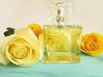 Pachnidło esenci aromata butelka świeża z żółtych róż dekoracją na drewnianym tle obraz stock