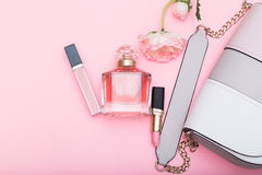 Pachnidło, wargi glosa, pomadka i torba na różowym tle, obrazy stock