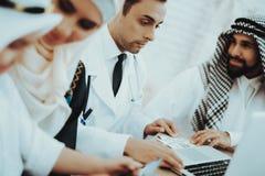Paciente árabe da família que dá o dinheiro para medicar fotografia de stock