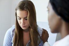 Paciente adolescente del doctor Talking To Unhappy en sitio del examen Imagen de archivo libre de regalías