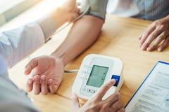 Paciente arterial del hombre de la presión arterial del doctor Measuring en atención sanitaria del brazo en hospital fotos de archivo libres de regalías