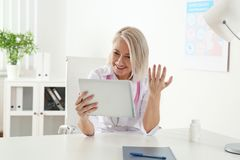 Paciente asesor del doctor que usa la charla video en la tableta imagen de archivo libre de regalías
