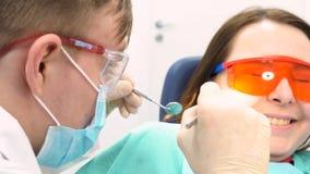 Paciente assustado com um doutor que tenta examiná-la em um escritório do dentista, conceito dos cuidados dentários media Uma moç fotos de stock royalty free