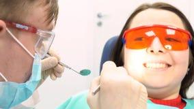 Paciente assustado com um doutor que tenta examiná-la em um escritório do dentista, conceito dos cuidados dentários media Uma moç foto de stock