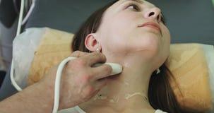Paciente caucásico joven de la mujer en sitio del diagnóstico del ultrasonido almacen de video