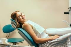 Paciente consideravelmente fêmea feliz no escritório dental fotografia de stock