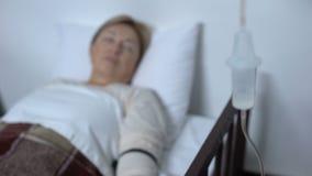 Paciente débil del pensionista que duerme en cama de hospital bajo tratamiento contrario del descenso almacen de metraje de vídeo