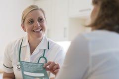 Paciente da fêmea de Discussing Leaflet With da enfermeira imagem de stock