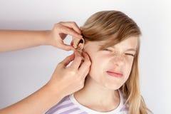 Paciente da moça não demasiado feliz quando mãos que introduzem uma audição Imagens de Stock