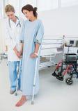 Paciente de ayuda del doctor en muletas en el hospital Foto de archivo