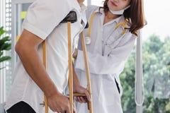 Paciente de ayuda del doctor de sexo femenino físico con las muletas en oficina del hospital fotografía de archivo