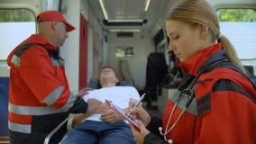 Paciente de examen en ensanchador, colega del paramédico que hace los expedientes, equipo de rescate metrajes