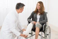 Paciente de Examining Leg Of del fisioterapeuta Imagen de archivo libre de regalías