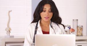 Paciente de fala do doutor latino-americano no portátil fotos de stock
