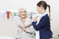 Paciente de Helping Smiling Senior do fisioterapeuta com mão Exercis fotografia de stock royalty free
