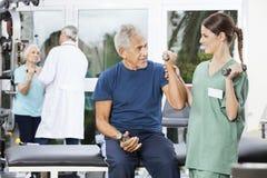 Paciente de Instructing Senior Male de la enfermera que ejercita con pesa de gimnasia imagen de archivo