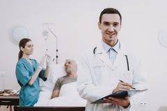 Paciente de la ayuda con el doctor Doctor con el viejo paciente imagen de archivo libre de regalías