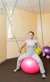 Paciente de la mujer joven que hace ejercicios físicos en un estudio de la rehabilitación mujer joven que hace ejercicios en bola Fotografía de archivo