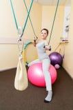 Paciente de la mujer joven que hace ejercicios físicos en un estudio de la rehabilitación mujer joven que hace ejercicios en bola Imagen de archivo