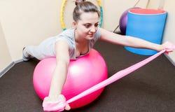 Paciente de la mujer joven que hace ejercicios físicos en un estudio de la rehabilitación mujer joven que hace ejercicios en bola Fotografía de archivo libre de regalías