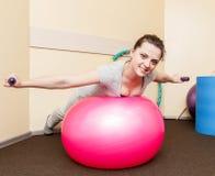 Paciente de la mujer joven que hace ejercicios físicos en un estudio de la rehabilitación mujer joven que hace ejercicios en bola Foto de archivo libre de regalías