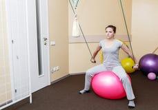 Paciente de la mujer joven que hace ejercicios físicos en un estudio de la rehabilitación mujer joven que hace ejercicios en bola Foto de archivo