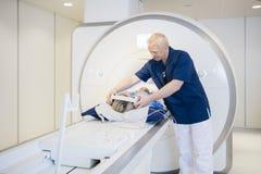 Paciente de Putting Headphones On do radiologista que submete-se à varredura de MRI fotos de stock