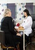 Paciente de While Sitting With do modelo do punho do doutor Looking At Rotator foto de stock