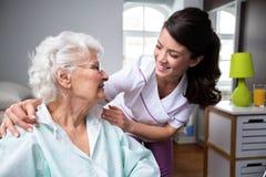 Paciente de sorriso da enfermeira e da mulher adulta na cadeira de rodas foto de stock royalty free