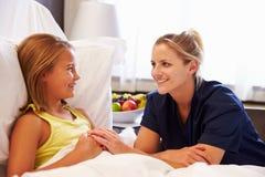Paciente de Talking To Child de la enfermera en cama de hospital Imagen de archivo libre de regalías